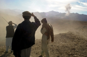 Anti-Taliban fighters from the Eastern Shura force survey a plume of smoke from a round dropped by a B-52 bomber on their enemy lines in the foothills of the Tora Bora mountains, where they are on the front lines of the fight against the remaining Al-Quaeda fores in the Nangarhar Province of Afghanistan on December 5, 2001. Photo by Yola Monakhov.